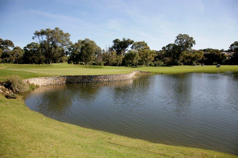 Jouez au golf l'étang photos stock