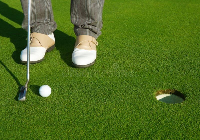 Jouez au golf l'homme vert de cours de trou mettant la bille courte image libre de droits