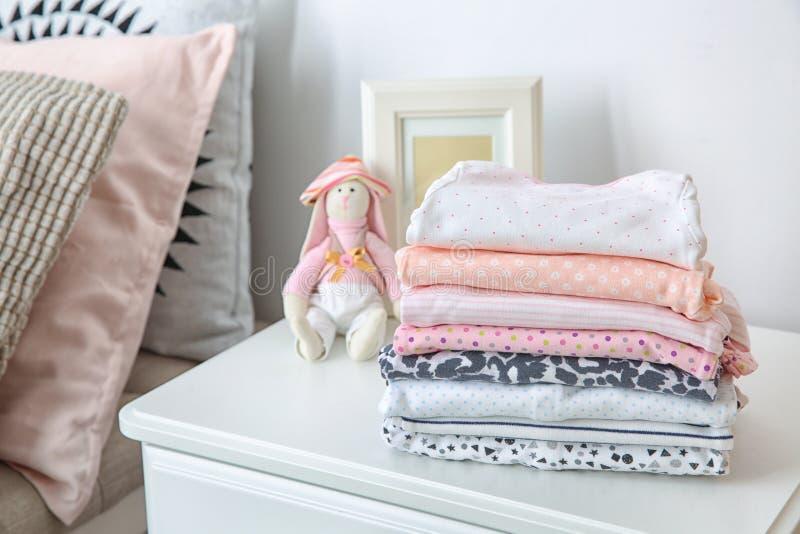 Jouez le lapin et la pile de vêtements d'enfant sur la table à l'intérieur photo stock