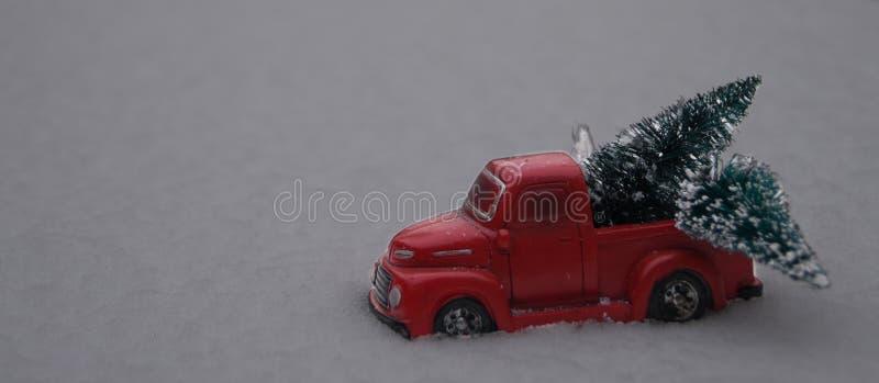 Jouez les arbres de Noël de chargement de camion pick-up dans la neige photographie stock