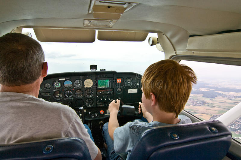 Joung boy is flying aircraft. Assisted by a trainer royalty free stock photo