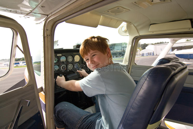 Joung boy in the pilot seat at. The airport royalty free stock photos