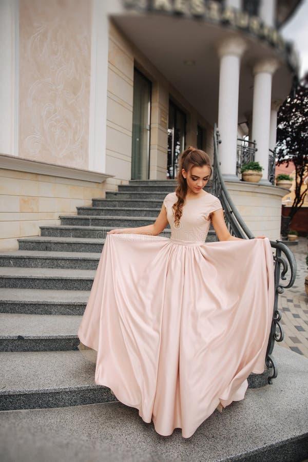Joung model z wielką wieczór suknią stał bezczynnie restaurację Brunetki dziewczyna pięknego włosianego styl i makeup obraz stock