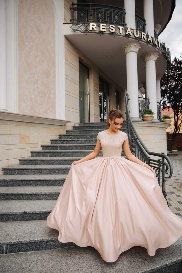 Joung model z wielką wieczór suknią stał bezczynnie restaurację Brunettegirl pięknego włosianego styl zdjęcia stock