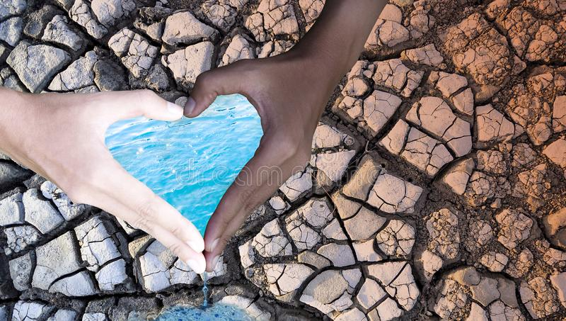 Jour d'environnement Les gens tiennent des mains dans la forme de coeur, avec l'eau et le sol sec sur le fond Concept de conserva photographie stock