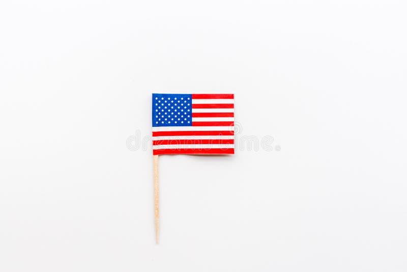 Jour de la Déclaration d'Indépendance 4 juillet heureux avec le mini drapeau des Etats-Unis se trouvant sur le fond blanc Vue sup images stock