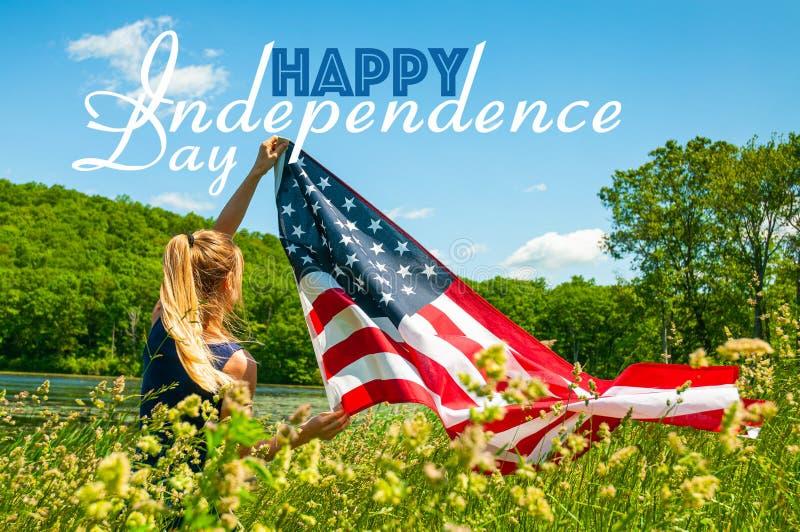 Jour de la D?claration d'Ind?pendance heureux, 4?me de juillet Femme tenant le drapeau am?ricain images libres de droits