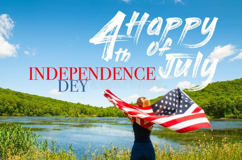 Jour de la D?claration d'Ind?pendance heureux, 4?me de juillet Jeune femme tenant le drapeau américain sur le fond de lac images stock