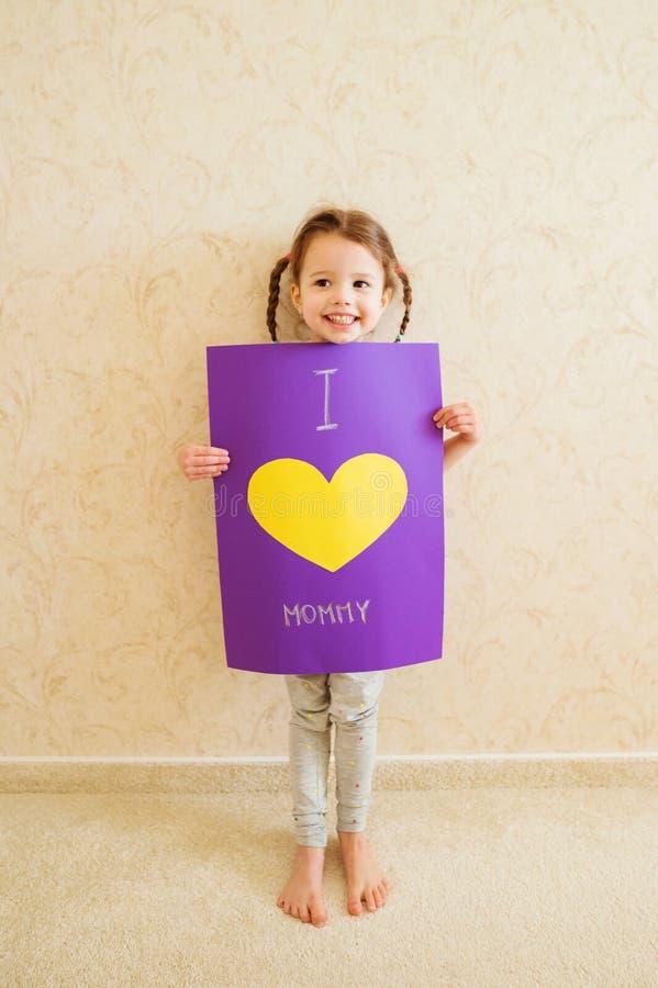 Jour de mères, fille tenant la carte de voeux pour sa maman photographie stock libre de droits