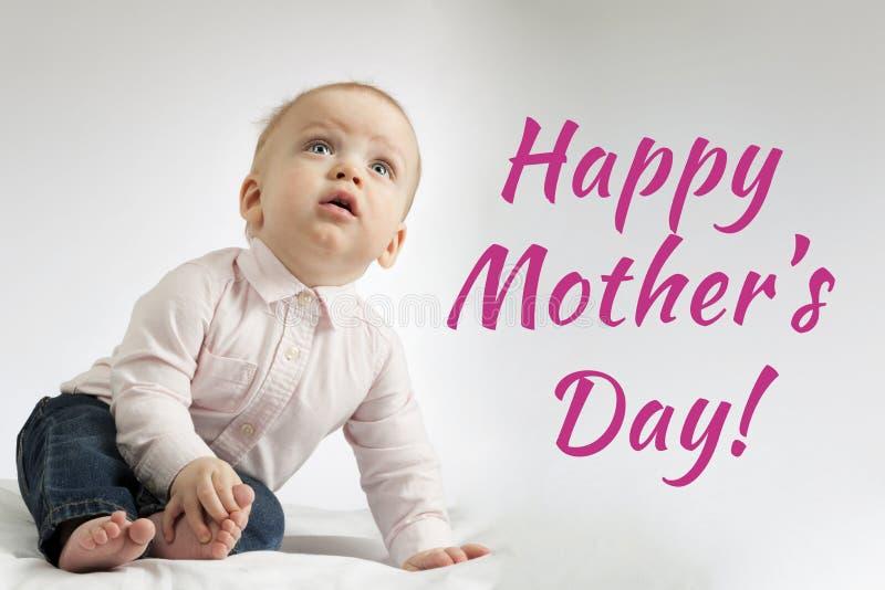 Jour de mères heureux Enfant en bas âge à bouche ouverte attentif s'asseyant sur la couverture et recherchant postcard photo stock