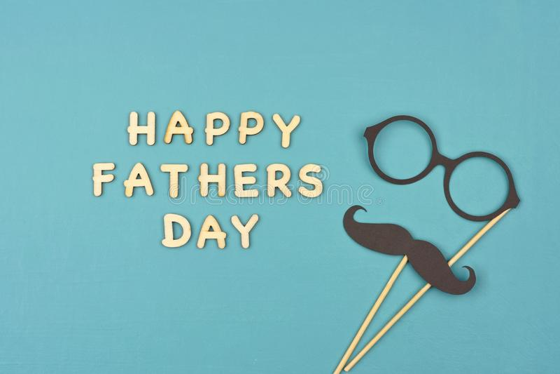 Jour de pères heureux avec la moustache et les verres au-dessus d'un fond bleu photos libres de droits