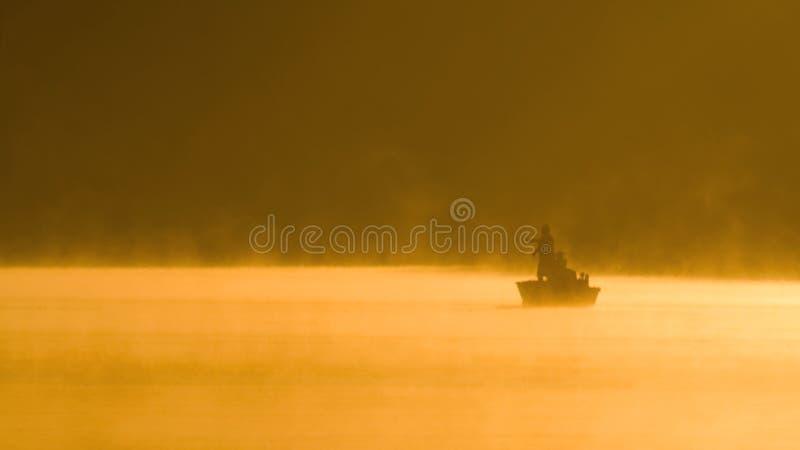 Jour de pêche brumeux sur un lac photographie stock libre de droits