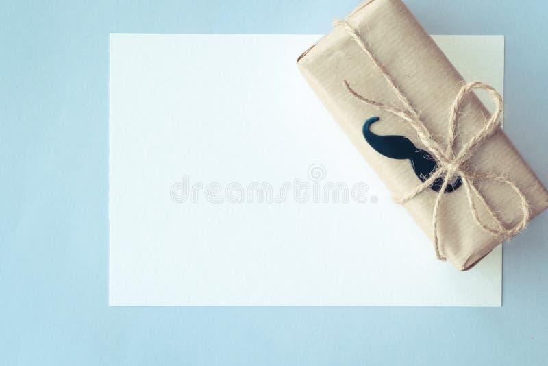 Jour de p?res Carte blanche et paquet de cadeau enveloppé avec le papier et la corde sur le fond bleu-clair Copyspace images libres de droits