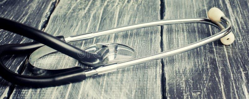 Jour de santé du monde, le concept de la médecine de la famille et assurance stéthoscope sur un fond en bois noir images libres de droits