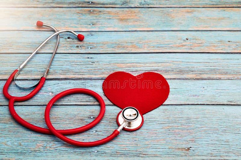 Jour de santé du monde, soins de santé et concept médical, stéthoscope rouge et coeur rouge sur le fond en bois bleu photo stock