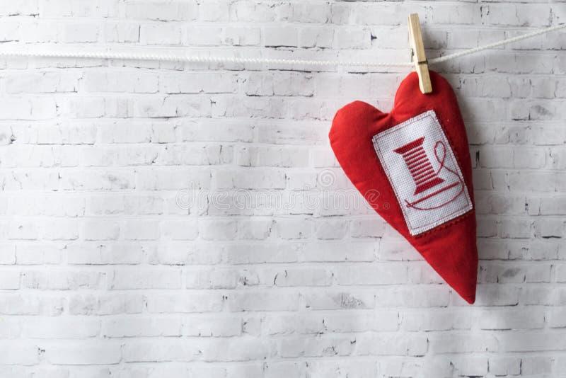 Jour de travail manuel Fond de mur de briques Le coeur rouge fait main de textile pèse sur une corde, attachée avec une pince à l photos stock