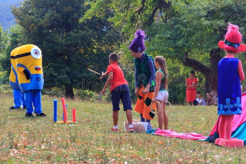 Jour de vacances du village Kamennomostsky avec terrains de jeu et concours du ` s d'animateurs et d'enfants en parc en automne photographie stock