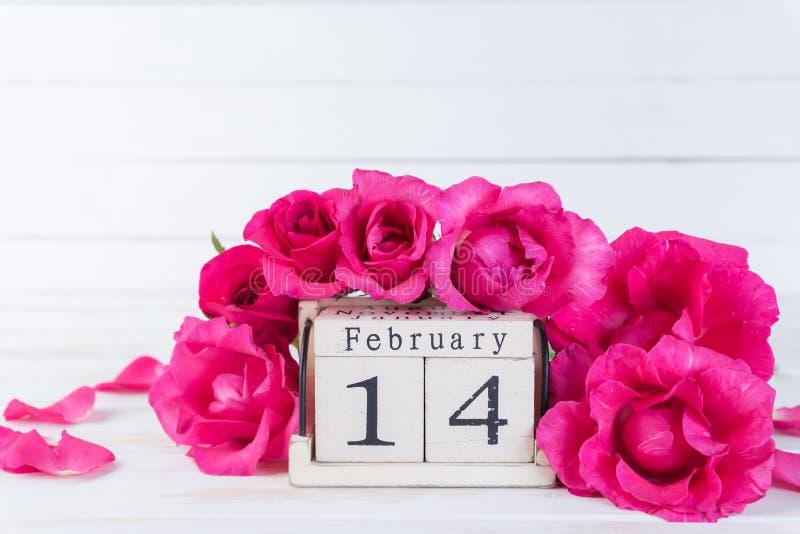 Jour de valentines et concept d'amour Roses roses avec le texte du 14 février sur le calendrier de bloc en bois sur le fond en bo images stock