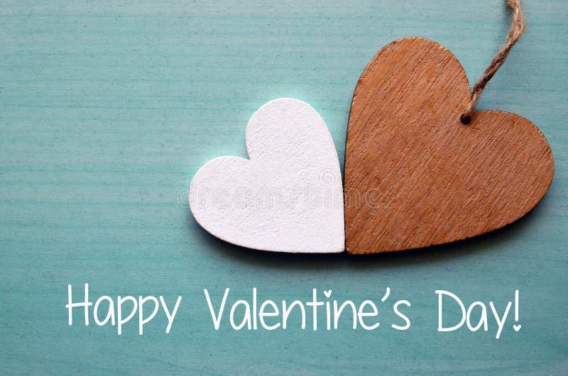 Jour de valentines heureux Deux coeurs en bois décoratifs sur un fond en bois bleu images stock