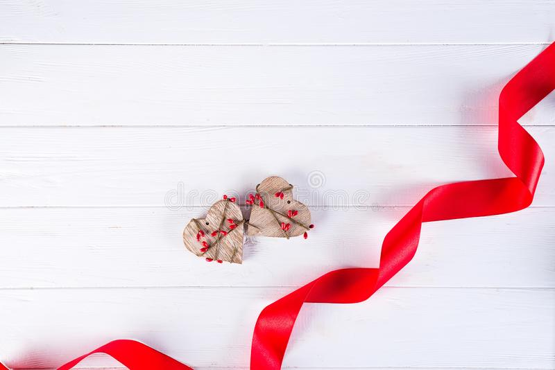 Jour de valentines heureux Ruban rouge et deux coeurs en bois sur le fond blanc Concept de jour de Valentines photographie stock libre de droits