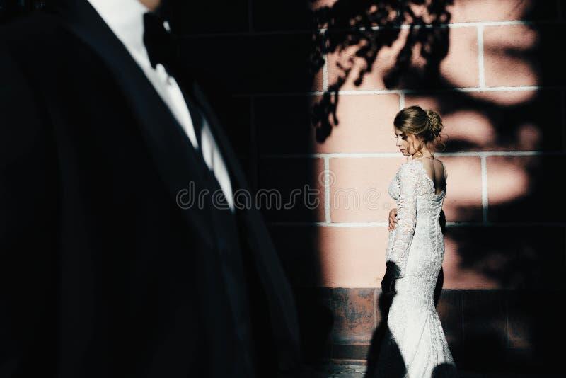 Jour du mariage Un jeune, bienveillant couple flânant autour de la ville et posant dans la perspective du mur rose images libres de droits