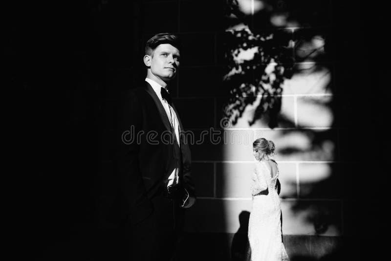 Jour du mariage Un jeune, bienveillant couple flânant autour de la ville et posant dans la perspective du mur rose photo stock