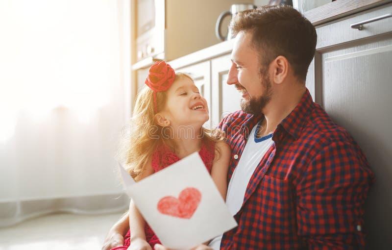 Jour du `s de père Fille heureuse de famille donnant la carte de voeux de papa photo stock