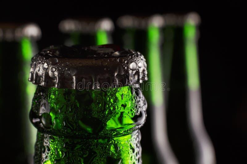 Jour du ` s de St Patrick Bière verte fraîche dans la bouteille avec des baisses de condensat sur un fond noir Concept : Bar, jou image libre de droits