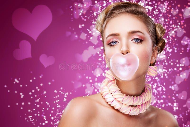 Jour du ` s de St Valentine Belle jeune fille blonde sexy de portrait soufflant le coeur rose du bubble-gum Des vacances rouges images libres de droits