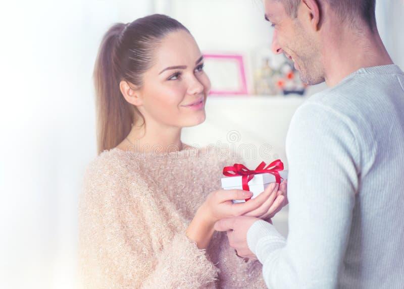 Jour du ` s de St Valentine Jeune homme donnant un cadeau à son amie photo libre de droits