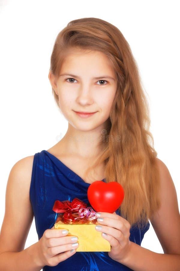 Jour du `s de Valentine Belle adolescente de sourire avec un cadeau et un coeur rouge symbolique regardant l'appareil-photo images libres de droits