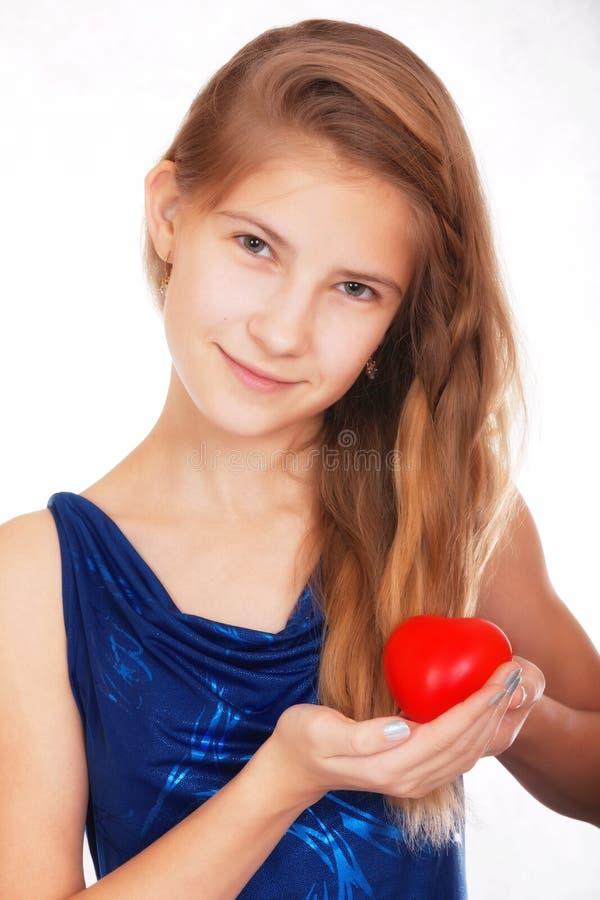 Jour du `s de Valentine Belle fille de l'adolescence de sourire avec un cadeau symbolique sous forme de coeur rouge photo libre de droits