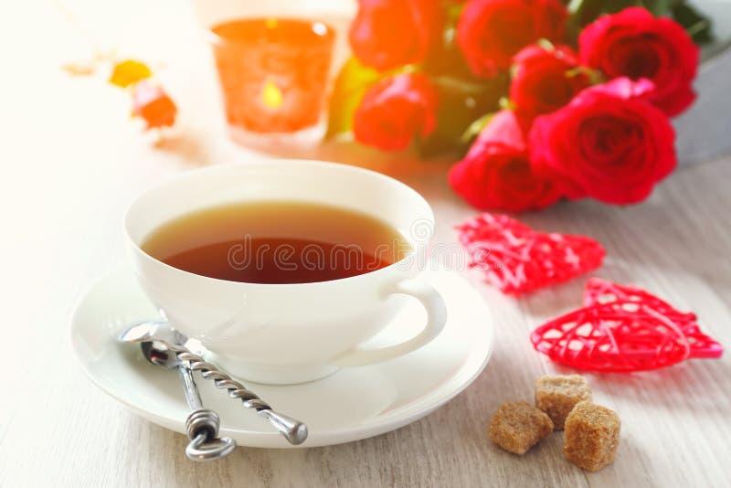 Jour du ` s de Valentine : Boisson romantique de thé avec la bougie et les roses rouges photographie stock