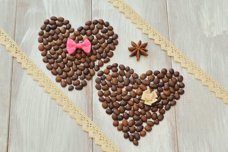 Jour du `s de Valentine Deux coeurs faits de grains de café avec le noeud papillon et la fleur décorative faits en satin, anis d' image stock