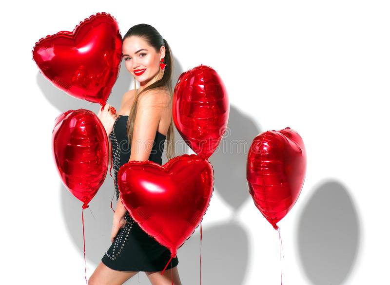 Jour du `s de Valentine Fille de beauté avec les ballons à air en forme de coeur rouges ayant l'amusement, d'isolement sur le bla photo libre de droits