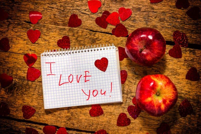 Jour du `s de Valentine JE T'AIME écrit sur le papier dans un carnet table en bois rustique et coeurs et pommes rouges image stock