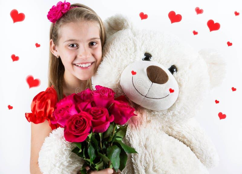 Jour du ` s de Valentine de saint Jolie fille avec la robe rouge, les roses rouges seau et le coeur image stock