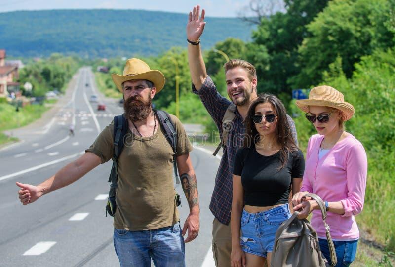 Jour ensoleillé de déplacement d'été d'auto-stoppeurs d'amis Essai de voyageurs pour arrêter la voiture Voyageurs d'amis de socié images libres de droits
