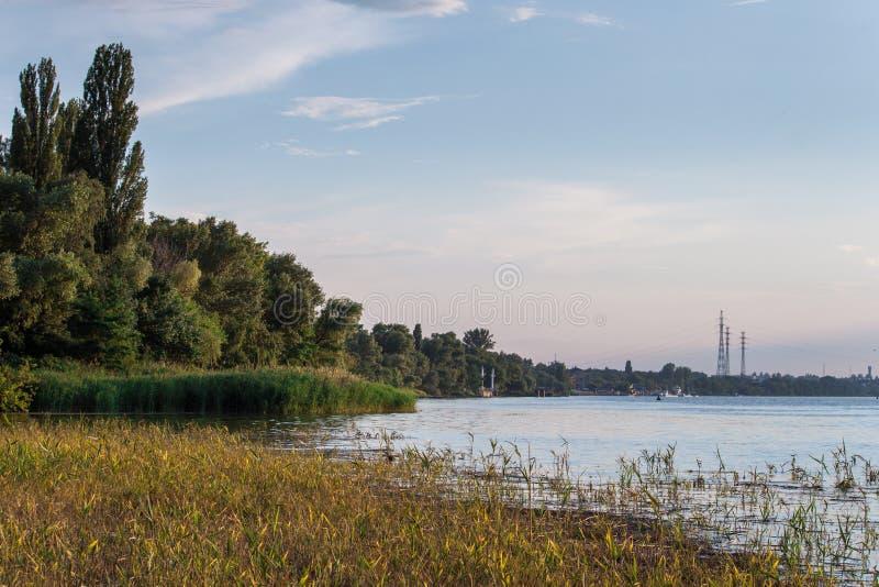 Jour ensoleillé sur une rivière calme avec des joncs en été Nova Kakhovka, Ukraine Lignes électriques à haute tension au coucher  photo stock