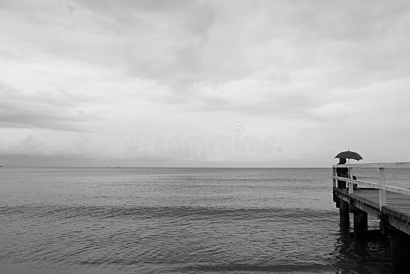 Jour gris sur la plage de Sopot Pologne et un homme sous un parapluie sur le pilier images stock