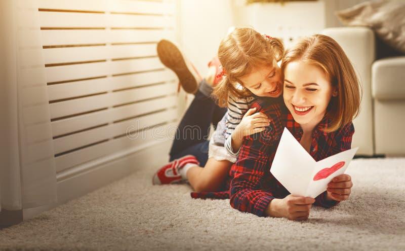 Jour heureux du ` s de mère ! La fille donne à sa mère une carte postale photographie stock libre de droits