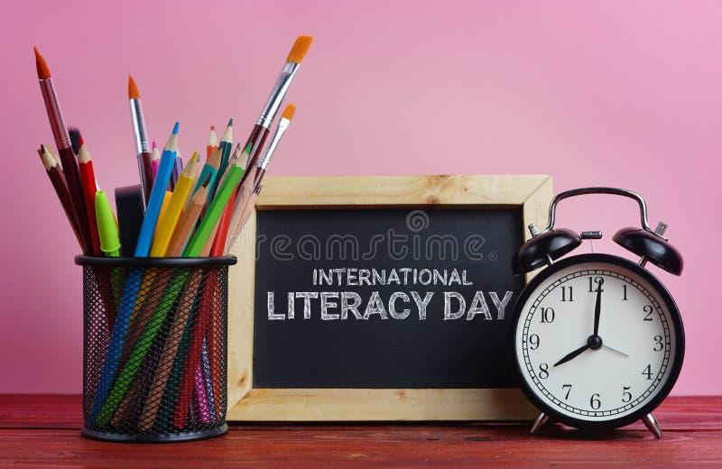 Jour international d'instruction Tableau noir, réveil et école S photo libre de droits
