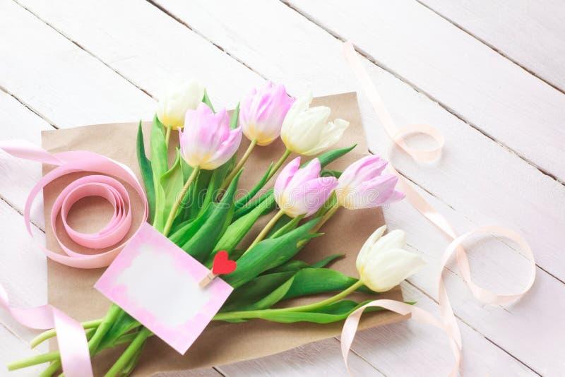 Jour international du ` s de femmes Un bouquet des tulipes blanches et roses avec un ruban sur un fond blanc Carte de voeux Resso image libre de droits