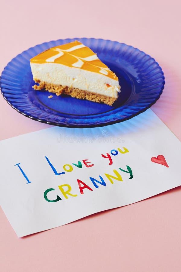 Jour national heureux de grands-parents Carte de voeux colorée faite par les enfants et le morceau de gâteau sur le plat bleu com photographie stock libre de droits