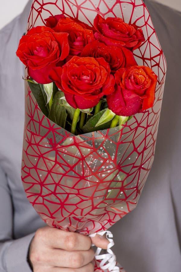 Jour ou proposition de valentines Jeune homme bel heureux tenant le grand groupe de roses rouges dans sa main sur le fond gris images stock