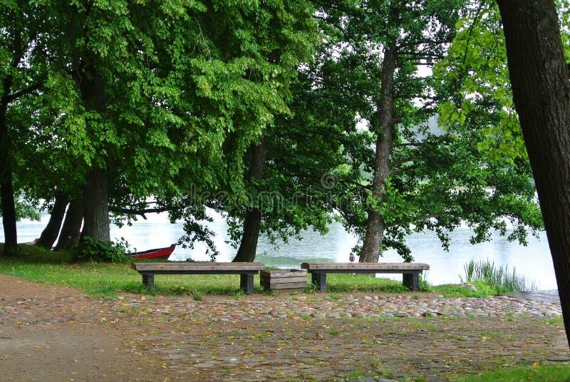Jour pluvieux au parc naturel de Trakai, une vue vers un lac, vieux grands arbres, bancs en bois et un bateau de pêche image stock