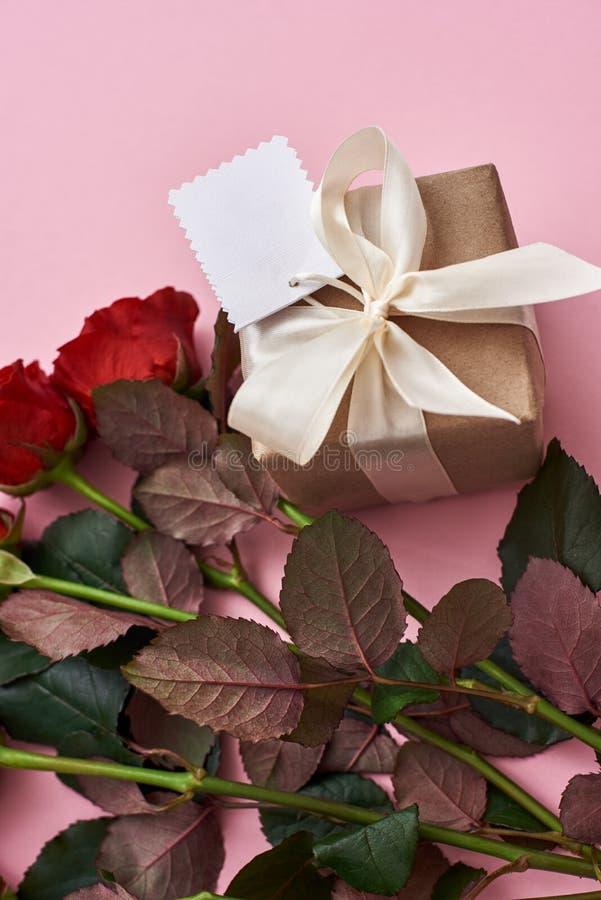 Jour pour célébrer leur amour Impressionnez-la avec les roses rouges fraîches et le beau boîte-cadeau image stock