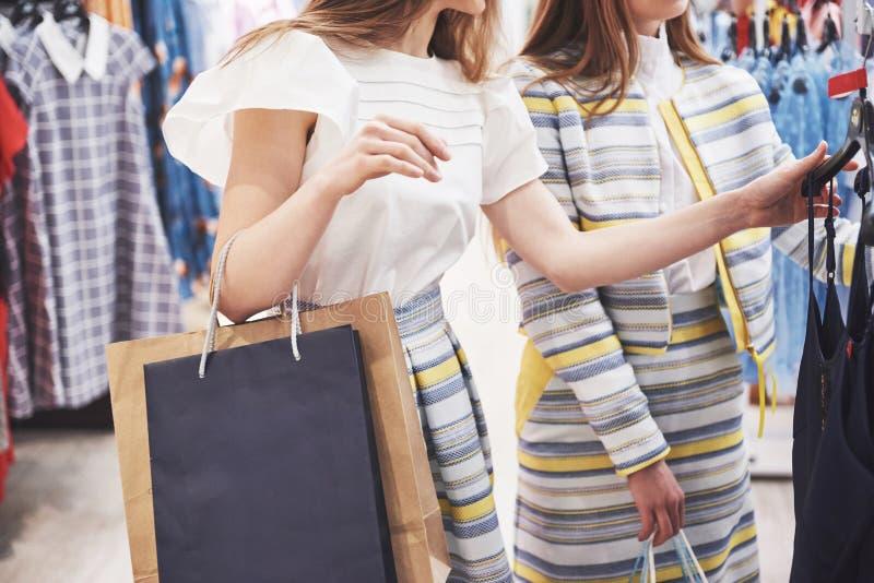 Jour splendide pour l'achat Deux belles femmes avec des sacs à provisions regardant l'un l'autre avec le sourire tout en marchant images stock