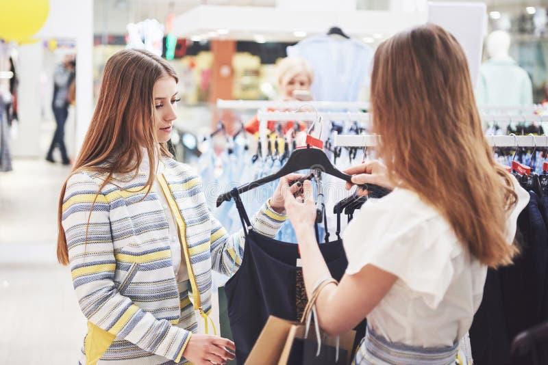 Jour splendide pour l'achat Deux belles femmes avec des sacs à provisions regardant l'un l'autre avec le sourire tout en marchant image stock