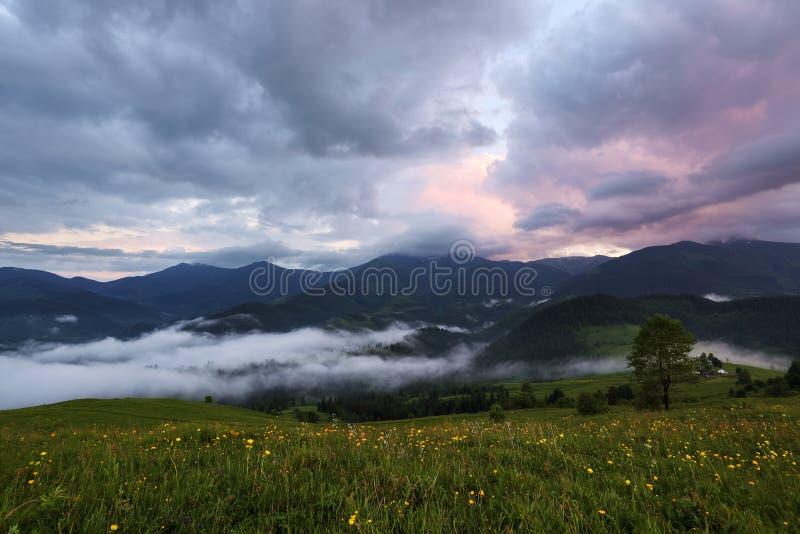 Journée de printemps majestueuse Un beau paysage avec de hautes montagnes, ciel avec des nuages et coucher du soleil Brouillard d photo stock